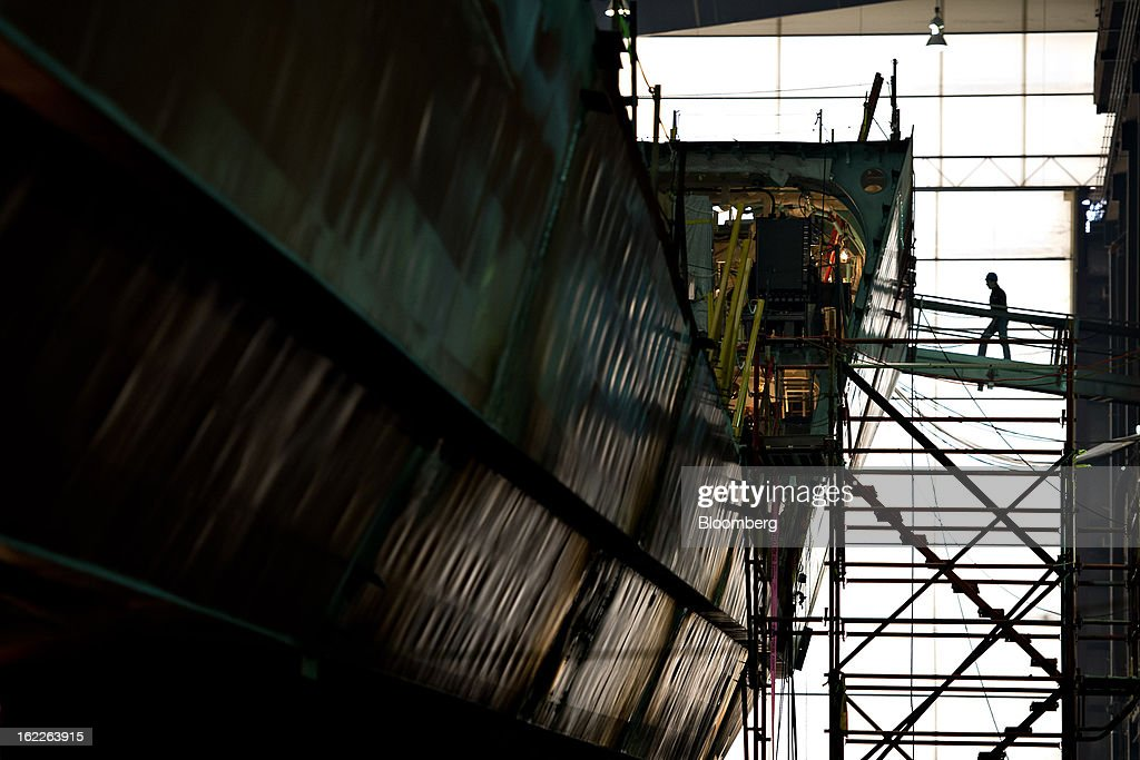 An employee walks across scaffolding surrounding a U.S. Navy Littoral Combat Ship (LCS) under construction at Marinette Marine Corp., in Marinette, Wisconsin, U.S., on Monday, Feb. 11, 2013. Marinette Marine Corp. makes one version of the Littoral Combat Ship in partnership with Lockheed Martin Corp. As the Pentagon faces $500 billion in spending cuts over a decade that are set to begin March 1, the $37 billion program to design and build Littoral Combat Ships may become a target for reductions that would take business from Lockheed and Austal Ltd., which also makes a version of the ship in partnership with General Dynamics Corp. at Austal's yard in Mobile, Alabama. Photographer: Daniel Acker/Bloomberg via Getty Images