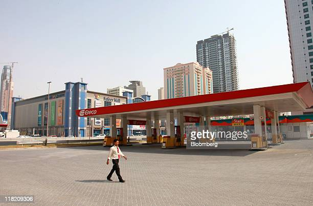 An employee walks across the forecourt of a closed gas station operated by Emirates Petroleum Products Co known as Eppco in Sharjah United Arab...