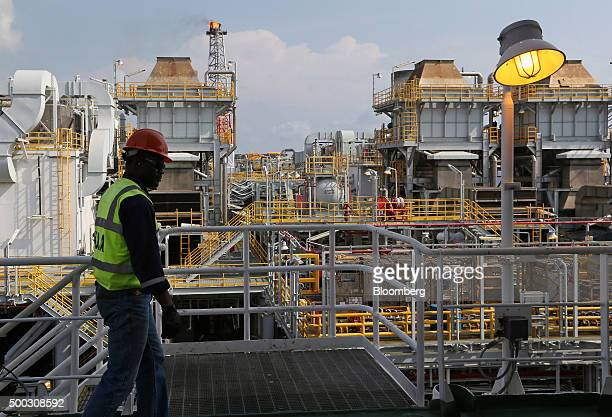 An employee walks along an upper level walkway aboard the Agbami floating oil production storage and offloading vessel operated by Chevron Corp in...
