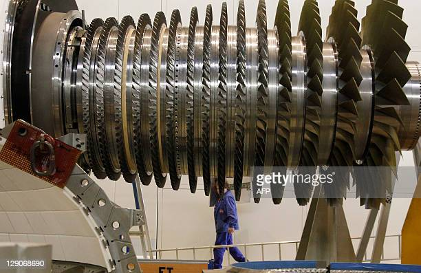 An employee walks behind the rotor of a Siemens AG Gas Turbine class H is seen at the German industrial giant Siemens historic construction plant on...