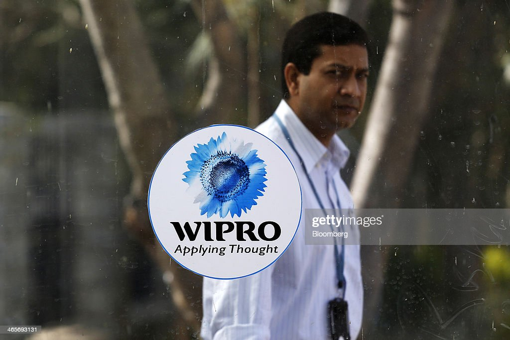 An employee walks behind the Wipro Ltd. logo displayed on a pane of glass at the company's campus in Bangalore, India, on Tuesday, Jan. 28, 2014. Worldwide spending on information technology will grow 3.1 percent to $3.8 trillion this year, with IT services set to climb 4.5 percent, researcher Gartner Inc. forecast Jan. 6. Photographer: Vivek Prakash/Bloomberg via Getty Images