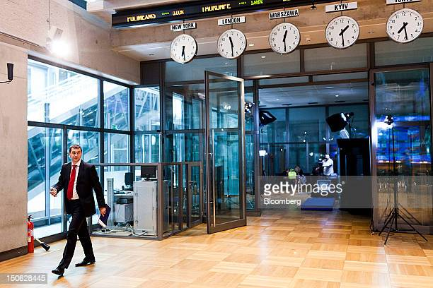 An employee walks beneath clocks displaying global time zones in the prices hall inside the Warsaw Stock Exchange in Warsaw Poland on Thursday Aug 23...