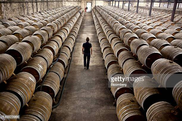 An employee walks between barrels of Remy Martin Fine Champagne Cognac laid to age in a cellar at the Remy Cointreau SA headquarters in Cognac France...