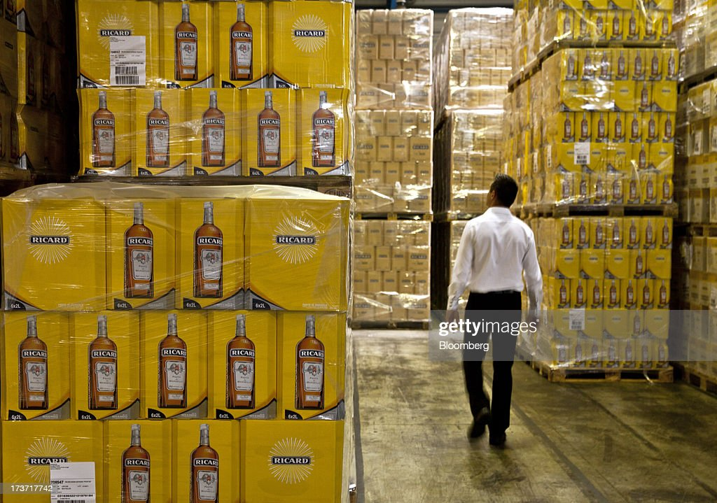 An employee walks between boxes of Ricard pastis, produced by Pernod Ricard SA, in the company's storage area in Bordeaux, France, on Tuesday, July 16, 2013. Distillers such as Diageo and Pernod Ricard SA are seeking to expand in emerging markets where booming economic growth is creating a burgeoning middle class with more disposable income. Photographer: Balint Porneczi/Bloomberg via Getty Images