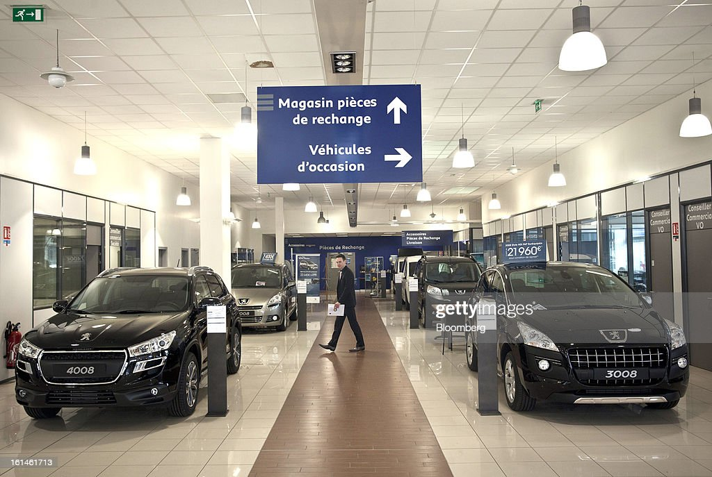 An employee walks between Peugeot automobiles on display in the showroom at the Peugeot Sial Toulouse dealership in Toulouse, France, on Monday, Feb. 11, 2013. Europe's car market is forecast to drop to 12.3 million vehicles this year, 23 percent below the pre-crisis peak, IHS Automotive research company estimates. Photographer: Balint Porneczi/Bloomberg via Getty Images
