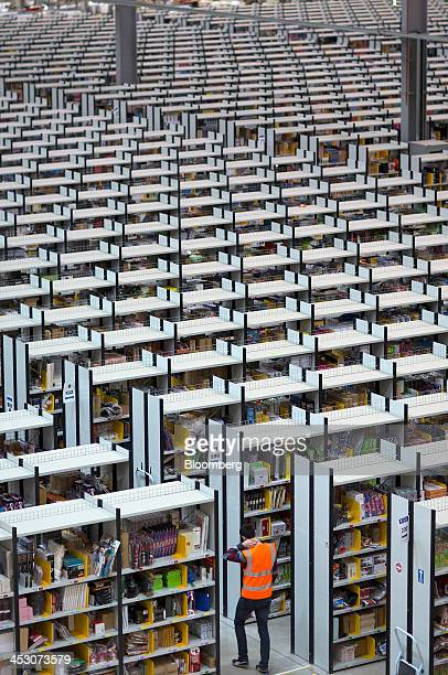 An employee walks between rows of storage racks at one of Amazoncom Inc's fulfillment centers in Rugeley UK on Monday Dec 2 2013 Online retailers in...