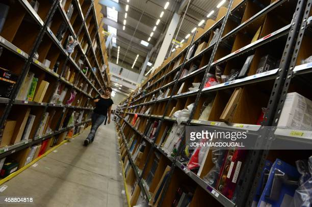 An employee walks between shelves where products are stored before distribution at US online retail giant Amazon's Brieselang logistics center west...
