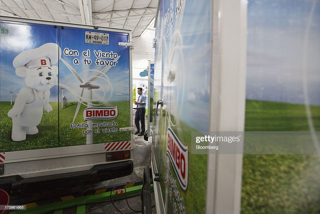 An employee walks between two electric delivery trucks inside Grupo Bimbo SAB de CV's new sales center in Mexico City, Mexico, on Thursday, July 18, 2013. Grupo Bimbo inaugurated a new eco-friendly sales center today. Photographer: Susana Gonzalez/Bloomberg via Getty Images