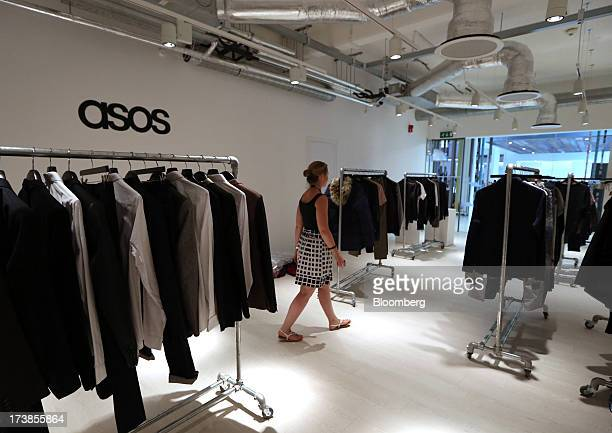 An employee walks by clothes hanging on rails at the headquarters of Asos Plc in London UK on Wednesday July 17 2013 Asos Plc the UK's largest...
