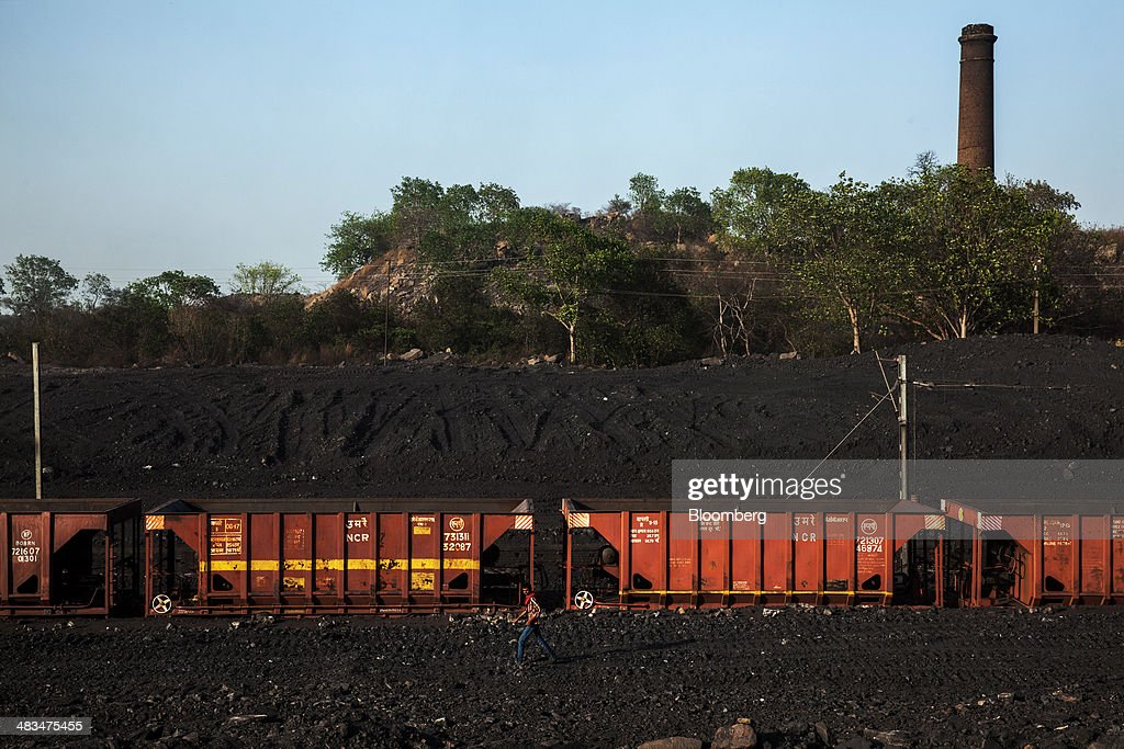 An employee walks by railcar wagons at a coal depot, operated by Coal India Ltd. subsidiary Bharat Coking Coal Ltd. (BCCL), in Jharia, Jharkhand, India, on Sunday, April 6, 2014. Coal India, the worlds largest producer, estimates on its website that the nation faces a supply deficit of 350 million tons by 2016-2017, thereby overtaking import demand from China, the worlds biggest coal consumer and producer. Photographer: Sanjit Das/Bloomberg via Getty Images