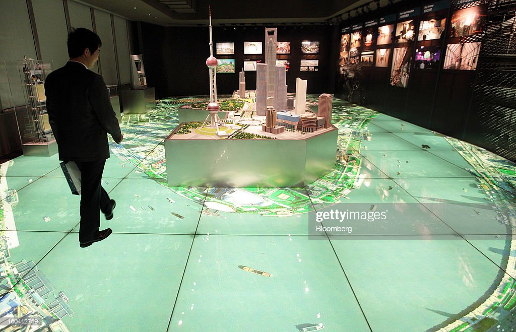An employee walks near a model of the Pudong area inside the Shanghai World Financial Center in Shanghai, China, on Wednesday, Jan. 30, 2013. China's economic growth accelerated for the first time in two years as government efforts to revive demand drove a rebound in industrial output, retail sales and the housing market. Photographer: Tomohiro Ohsumi/Bloomberg via Getty Images