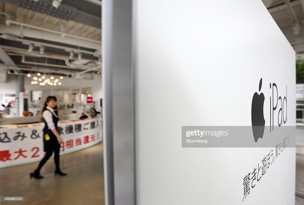 An employee walks near an advertisement for the Apple Inc. iPad at an NTT Docomo Inc. store in Tokyo, Japan, on Tuesday, June 10, 2014. NTT Docomo, Japan's largest wireless carrier by subscribers, began offering Apple Inc's iPad today. Photographer: Tomohiro Ohsumi/Bloomberg via Getty Images