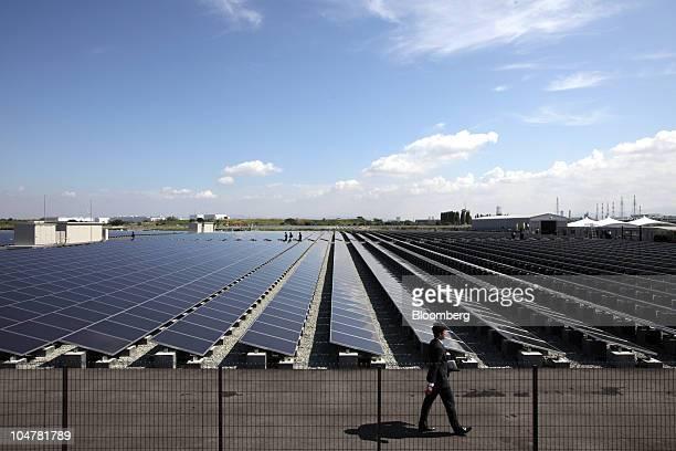 An employee walks near solar panels manufactured by Sharp Corp at Kansai Electric Power Co's mega solar power station in Sakai City Osaka Japan on...