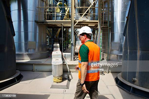 An employee walks near the preheater tower at Holcim Ltd's cement plant in Untervaz Switzerland on Wednesday July 2013 Holcim Chief Executive Officer...