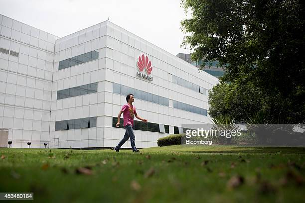 An employee walks past a building at the Huawei Technologies Co campus in the Longgang district of Shenzhen China on Wednesday Aug 6 2014 Huawei is...