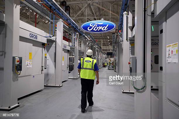 An employee walks past a Ford logo in the yettobecompleted engine production line at a Ford factory on January 13 2015 in Dagenham England Originally...
