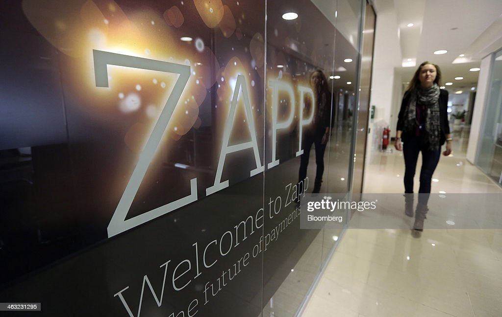 An employee walks past a logo inside the offices of Zapp, a money transfer and payment system, in this arranged photograph at the company's offices in London, U.K., on Thursday, Jan. 16, 2014. Zapp, a unit of Vocalink Ltd., has created a system that will allow customers of major banking institutions to see their balance and pay for goods in real-time. Photographer: Chris Ratcliffe/Bloomberg via Getty Images