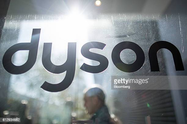 An employee walks past a logo on the staff entrance to the Dyson Ltd campus in Malmesbury UK on Wednesday Oct 5 2016 In addition to cordless cleaning...