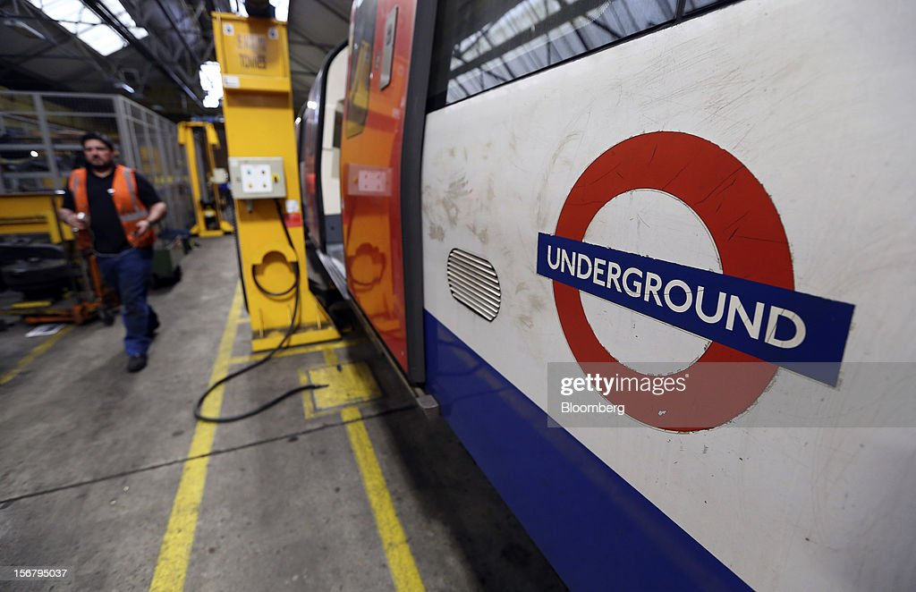 An employee walks past a London Underground Northern Line train at Alstom SA's Traincare Centre in the Golders Green district of London, U.K., on Wednesday, Nov. 21, 2012. Transport for London (TFL), who oversee the U.K. capital's public transport system, issued 300 million pounds ($476 million) of bonds five months ahead of schedule to take advantage of investor demand as it continues its 35 billion-pound transport investment program. Photographer: Chris Ratcliffe/Bloomberg via Getty Images
