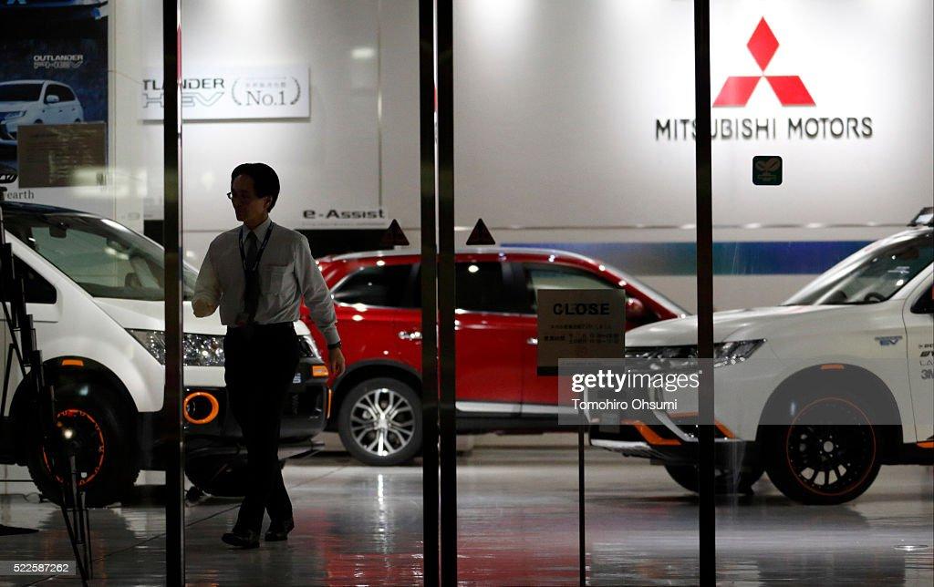 An employee walks past a Mitsubishi Motors vehicles displayed at the company's headquarters on April 20 2016 in Tokyo Japan Mitsubishi Motors share...