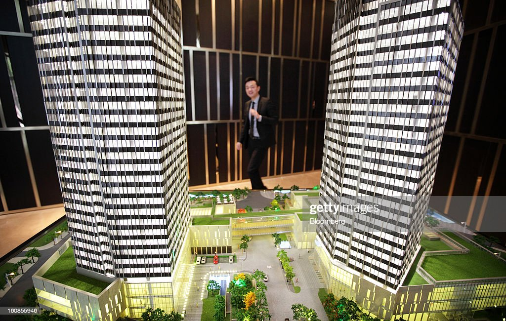An employee walks past a scale model showing Shui On Land Ltd. developments at a showroom in Shanghai, China, on Wednesday, Feb. 6, 2013. China's economic growth accelerated for the first time in two years as government efforts to revive demand drove a rebound in industrial output, retail sales and the housing market. Photographer: Tomohiro Ohsumi/Bloomberg via Getty Images