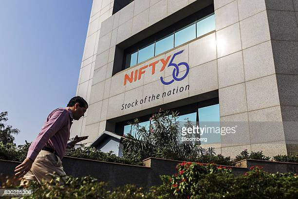 An employee walks past a signage for the CNX Nifty Index displayed on the National Stock Exchange of India Ltd building in Mumbai India on Friday Dec...