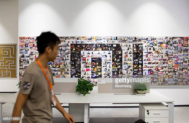 An employee walks past a wall displaying photographs inside a Xiaomi Corp office in Beijing China on Friday Sept 12 2014 Xiaomi Chief Executive...