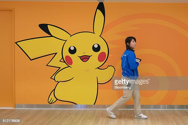 An employee walks past a wall featuring the Pikachu character at the Pokemon Center Mega Tokyo store in Tokyo Japan on Wednesday Feb 24 2016 Pokemon...