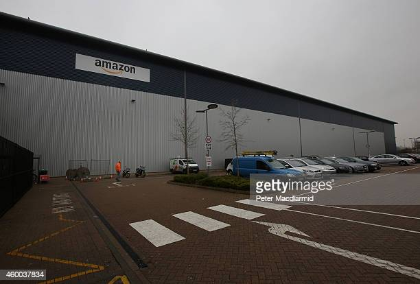 An employee walks past Amazon's warehouse on December 5 2014 in Hemel Hempstead England In the lead up to Christmas Amazon is experiencing the...