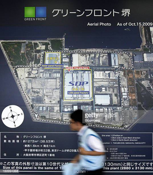 An employee walks past an aerial photo of the Sakai Display Products Corp plant displayed inside the plant in Sakai City Osaka Japan on Thursday Aug...