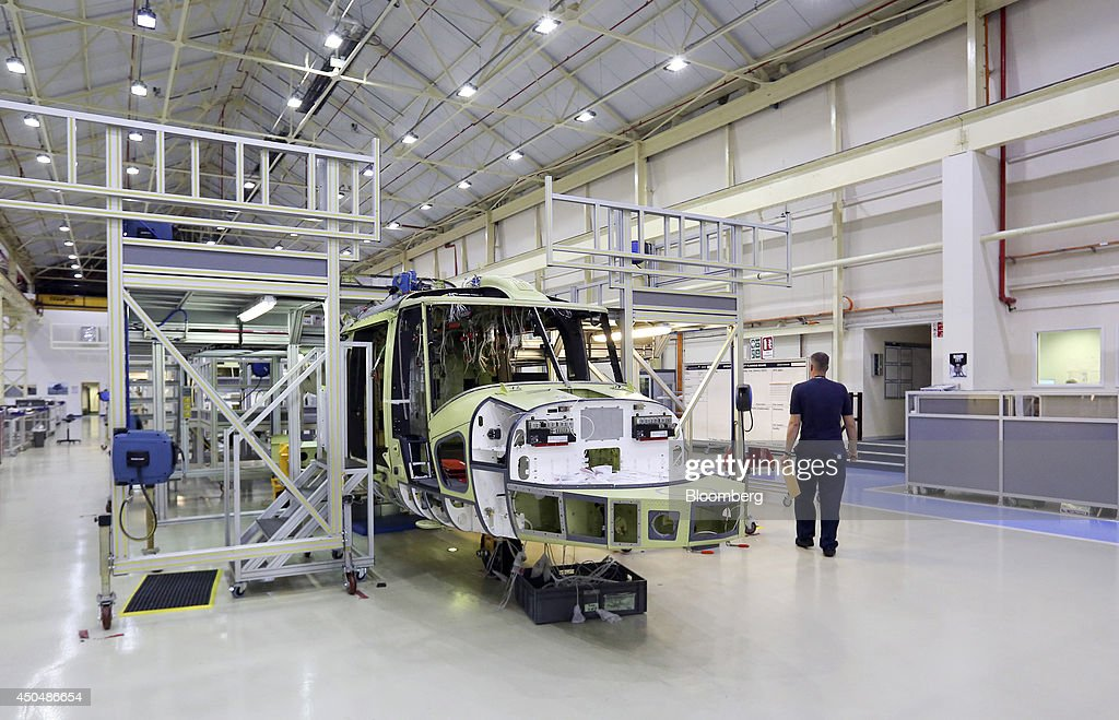 An employee walks past an AW159 helicopter, produced by AgustaWestland, a unit of Finmeccanica SpA, during production at the company's plant in Yeovil, U.K., on Thursday, June 12, 2014. U.K. unemployment declined more than expected and industrial production rose at the fastest annual pace since 2011, according to reports released this week. Photographer: Chris Ratcliffe/Bloomberg via Getty Images