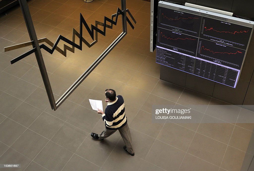 An employee walks past an electronic display at the Athens stock exchange on October 27 2011 Greece reacted with measured relief on Thursday after...