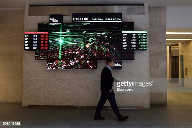 An employee walks past an illuminated screen depicting share price information for stocks on the London Stock Exchange as it stands in the atrium of...