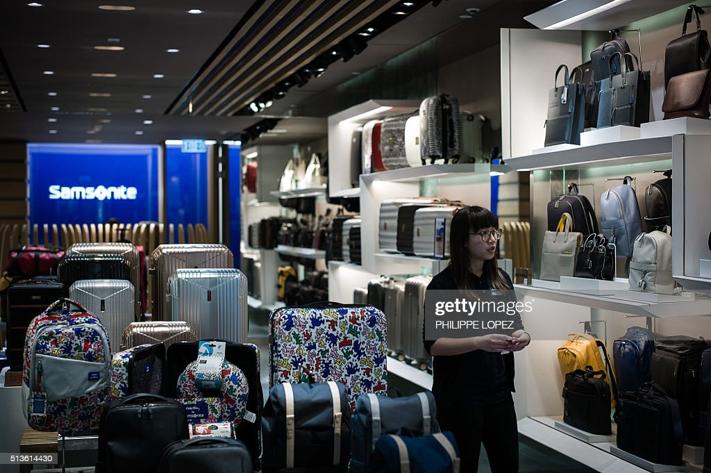 An employee walks past bags at a shop for luggage giant Samsonite ...