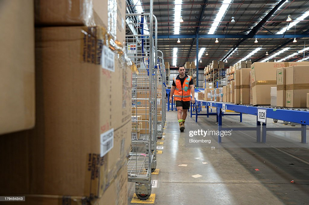 An employee walks past boxes of merchandise waiting to be transferred onto trolleys at the Myer Holdings Ltd. distribution center in Melbourne, Australia, on Tuesday, Sept. 3, 2013. A Bureau of Statistics report released in Sydney on Sept. 4 showed household spending climbed 0.4 percent in the second quarter, adding 0.2 percentage point to gross domestic product growth. Photographer: Carla Gottgens/Bloomberg via Getty Images