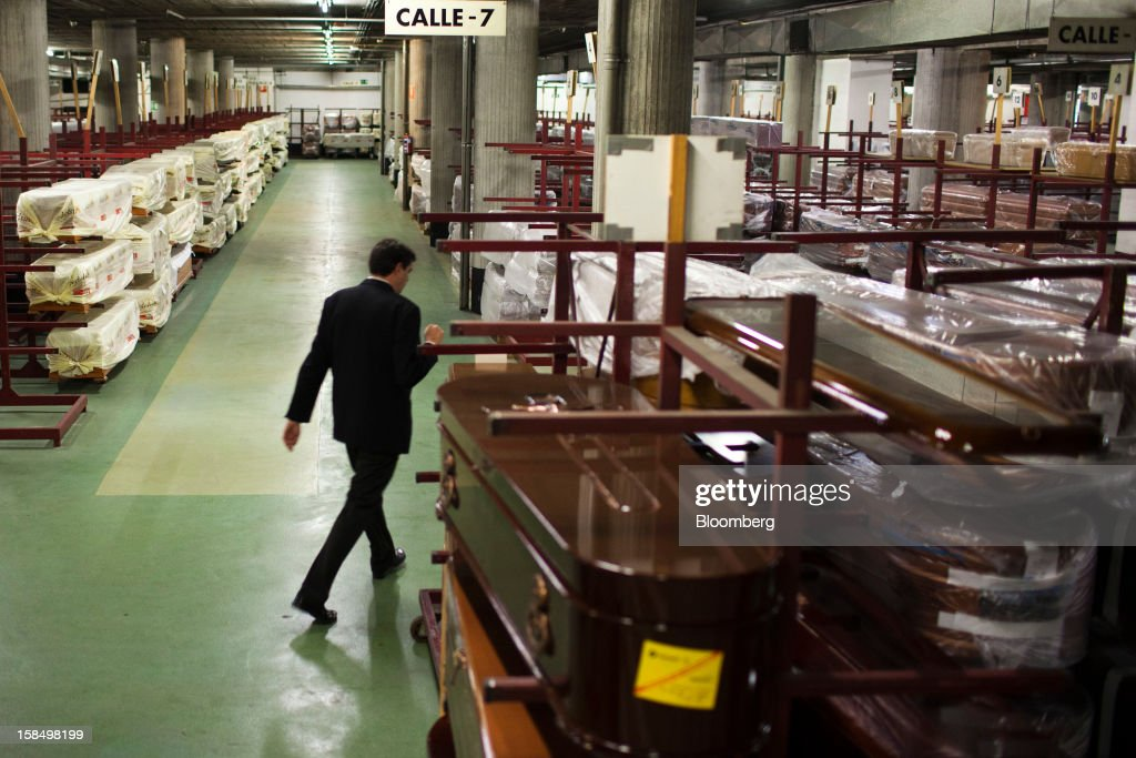 An employee walks past coffins stored on racks in the warehouse of the Empresa Mixta de Servicios Funerarios de Madrid SA funeral parlour in Madrid, Spain, on Monday, Dec. 17, 2012. Spain, responding to street protests and reports of suicides linked to foreclosures, introduced rules to help protect families from eviction, increasing the risk of creditor losses and weakening an already fragile banking system. Photographer: Angel Navarrete/Bloomberg via Getty Images