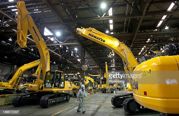 An employee walks past Komatsu Ltd excavators on the production line of the company's plant in Hirakata City Osaka Japan on Thursday Feb 23 2012...