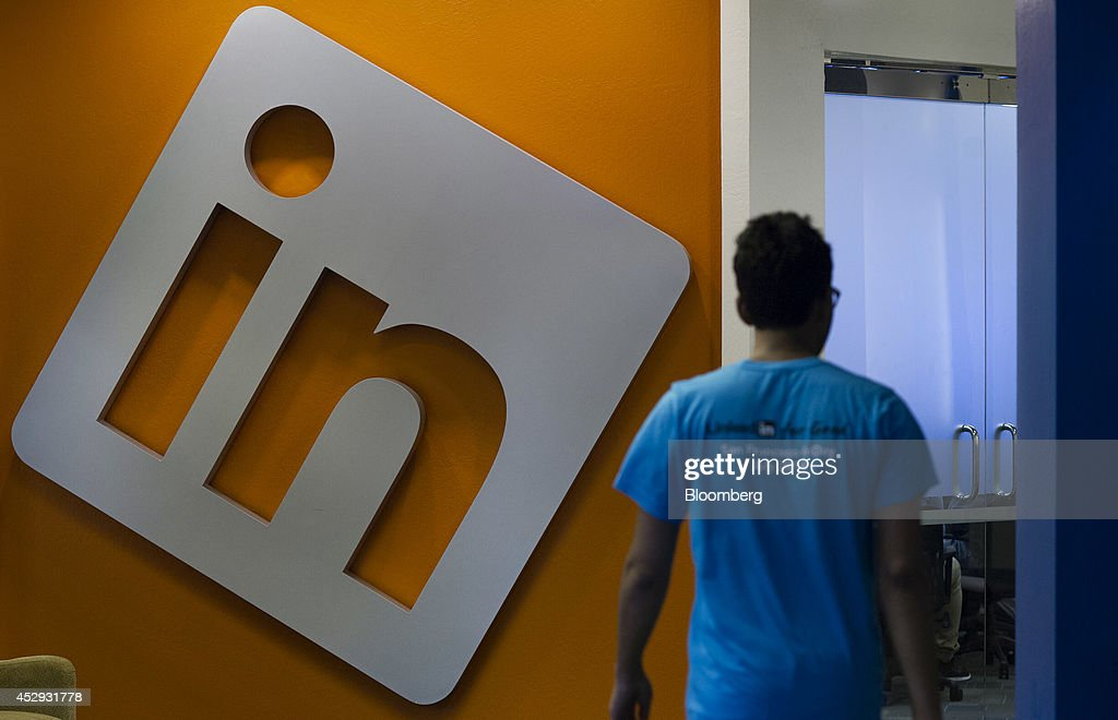 An employee walks past signage displayed on a wall at LinkedIn Corp. headquarters in Mountain View, California, U.S., on Monday, July 28, 2014. LinkedIn Corp. is scheduled to release earnings figures on July 31. Photographer: David Paul Morris/Bloomberg via Getty Images