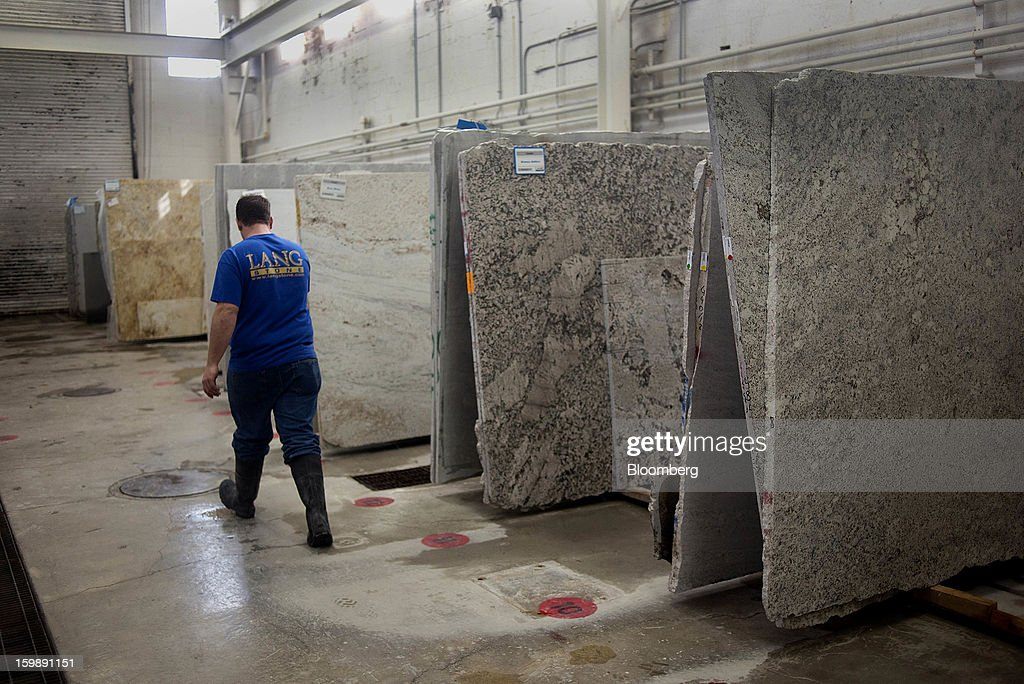 An employee walks past slabs of granite in the manufacturing area at the Lang Stone Co. facility in Columbus, Ohio, U.S., on Friday, Jan. 18, 2013. The Lang Stone Co. drafting department serves architects, builders, masonry contractors and homeowners, by providing design options and producing scaled and fully-detailed drawings for fabrication and installation. Photographer Ty Wright/Bloomberg via Getty Images