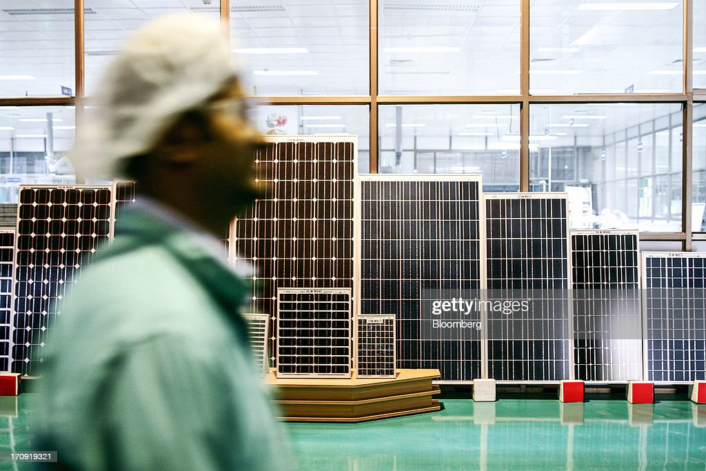 An employee walks past solar panels displayed at the Tata Power Solar Systems Ltd. manufacturing plant in Bangalore, India, on Tuesday, June 11, 2013. Tata Groups solar unit is expanding its business building plants for customers, forecasting that offices and factories will be paying more for grid power than solar by 2016 in most Indian states. Photographer: Dhiraj Singh/Bloomberg via Getty Images