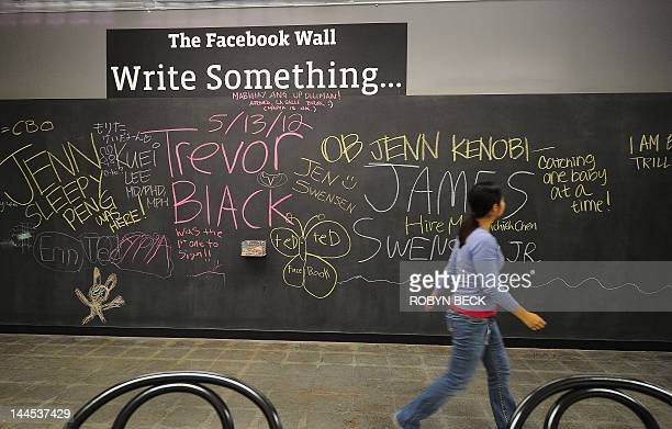 An employee walks past 'The Facebook Wall' a chalkboard on which employees can write or draw whatever they want at the Facebook campus in Menlo Park...