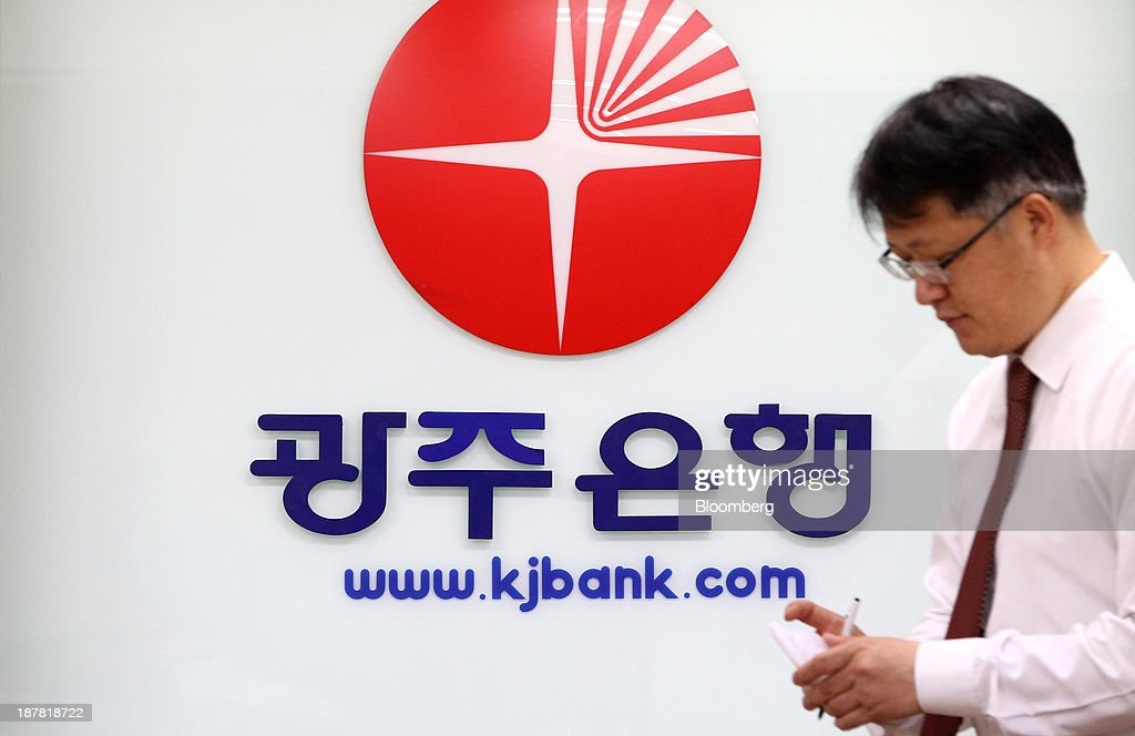 An employee walks past the logo of Kwangju Bank, a unit of Woori Finance Holdings Co., displayed inside one of the bank's branches in Seoul, South Korea, on Tuesday, Nov. 12, 2013. Woori Finance Holdings is scheduled to report third-quarter results on Nov. 14. Photographer: SeongJoon Cho/Bloomberg via Getty Images