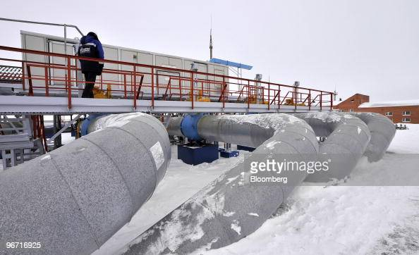 An employee walks past the monitoring station and gas pipelines at the gas compressor facility operated by OAO Gazprom in Sudzha Russia on Thursday...