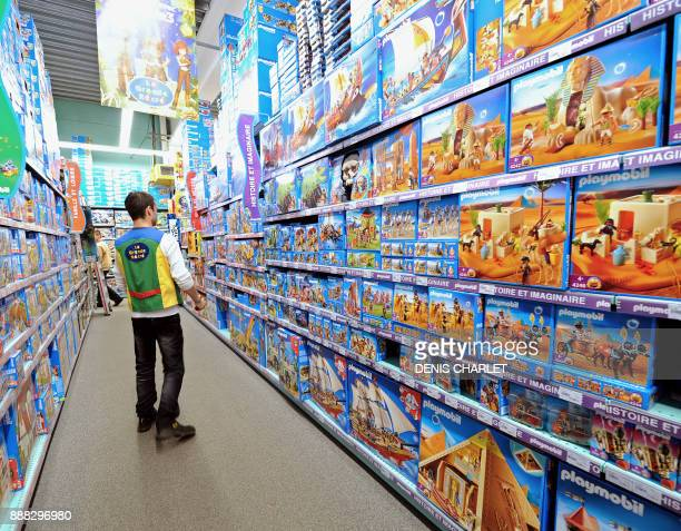 An employee walks past the shelves of La Grande Recre toys departement store in the French northern city of BruaylaBuissiere on November 20 2010 As...