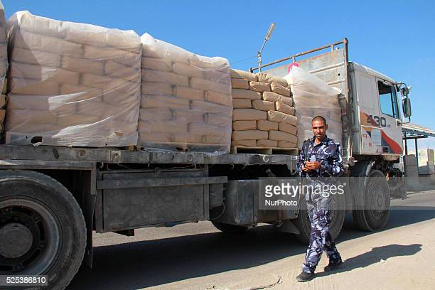 An employee walks past trucks loaded with bags of cement entering the Gaza Strip from Israel through the Kerem Shalom crossing on October 14 in Rafah...
