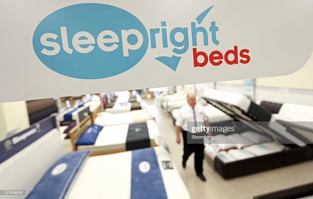 An employee walks through a display of sleepright beds inside a Carpetright Plc carpet store in Basildon, U.K., on Friday, June 21, 2013. U.K. retail sales rose more than economists forecast in May as consumers spent more online and food sales increased at their fastest pace for more than two years. Photographer: Chris Ratcliffe/Bloomberg via Getty Images