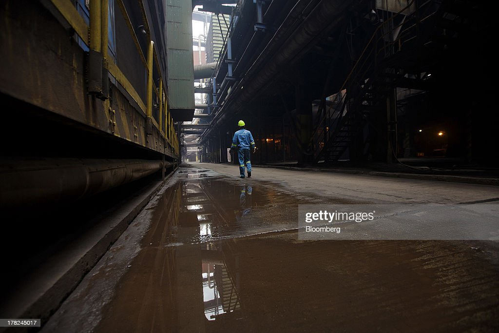 An employee walks through a passageway at ArcelorMittal's steel plant in Ostrava, Czech Republic, on Monday, Aug. 26, 2013. ArcelorMittal, the world's biggest steelmaker, said steel shipments will rise 1 percent to 2 percent this year compared with an earlier forecast of 2 percent in May. Photographer: Martin Divisek/Bloomberg via Getty Images