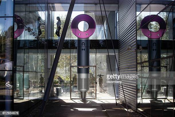 An employee walks through an elevated walkway decorated with a giant supersonic hair dryer in the Dyson Ltd campus in Malmesbury UK on Wednesday Oct...
