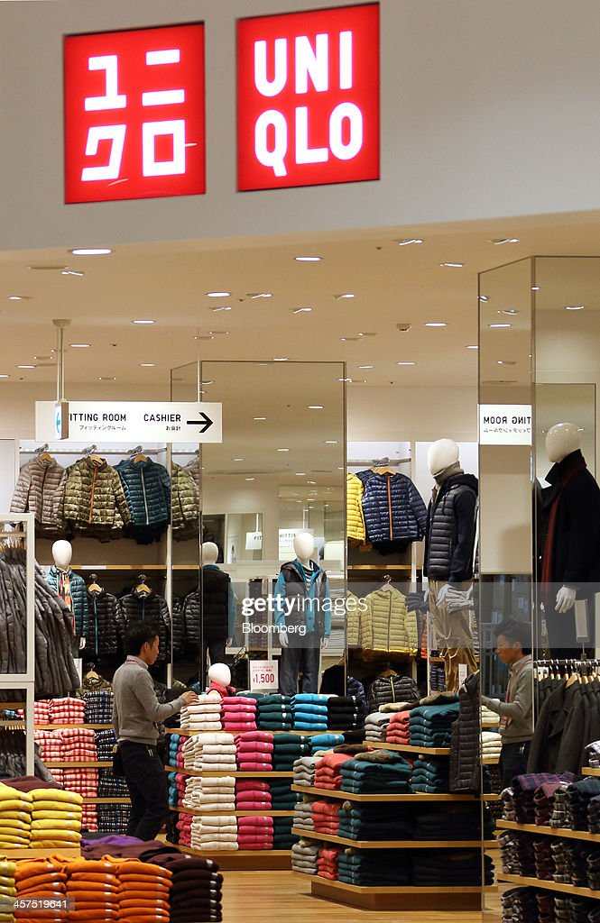 An employee walks through Fast Retailing Co.'s Uniqlo store inside Aeon Mall Makuhari Shintoshin shopping mall, operated by Aeon Mall Co., during a media preview ahead of the mall's opening in Chiba, Japan, on Monday, Dec. 16, 2013. Large Japanese businesses pared their projections for capital spending this fiscal year, signaling challenges for Abenomics as a sales-tax increase looms in April. Photographer: Tomohiro Ohsumi/Bloomberg via Getty Images