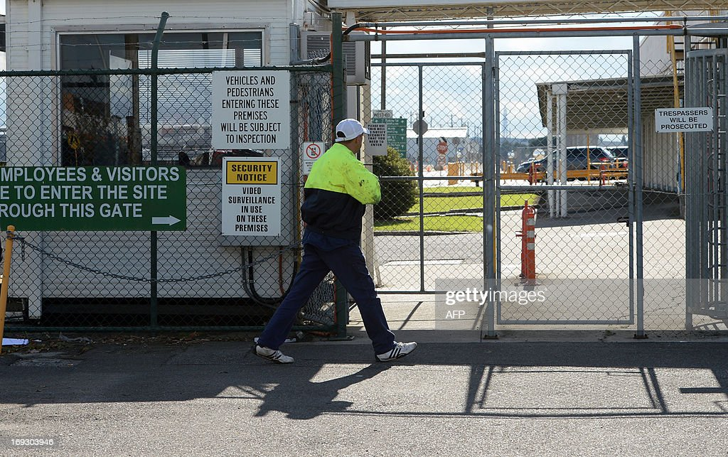 An employee walks towards to the site entrance of Ford's head office in Melbourne on May 23, 2013, as Ford announced it would cease making vehicles at its unprofitable Australian plants in 2016 and axe 1,200 jobs, ending an era that began in 1925 with the firm's first local car. Ford Australia chief executive Bob Graziano made the announcement as he revealed losses of 141 million AUSD (136 million USD) after tax in the last financial year and 600 million AUSD over the last five years. AFP PHOTO / Mal Fairclough